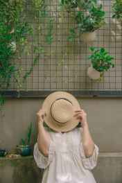 person wearing white elbow sleeved top covering beige sun hat